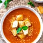 Bowl of Tomato basil soup with crouton and basil leaves