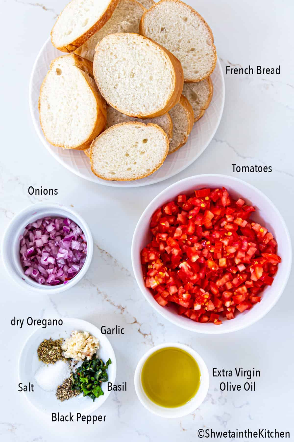 Ingredients for Tomato Basil Bruschetta on white surface