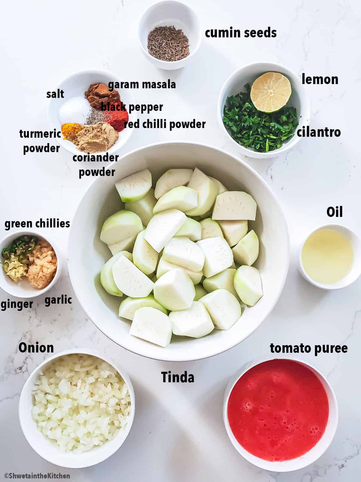 top view of Punjabi Tinda curry ingredients placed in bowls on white surface