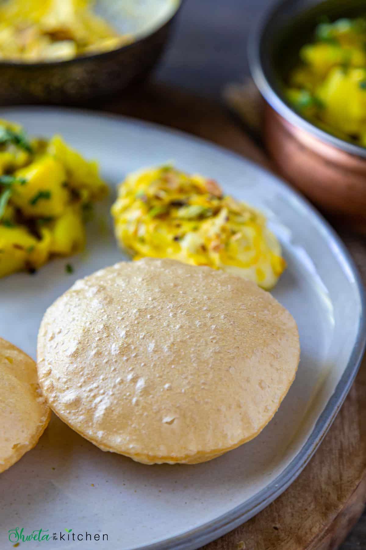 Puri on a plate with shrikhand on side