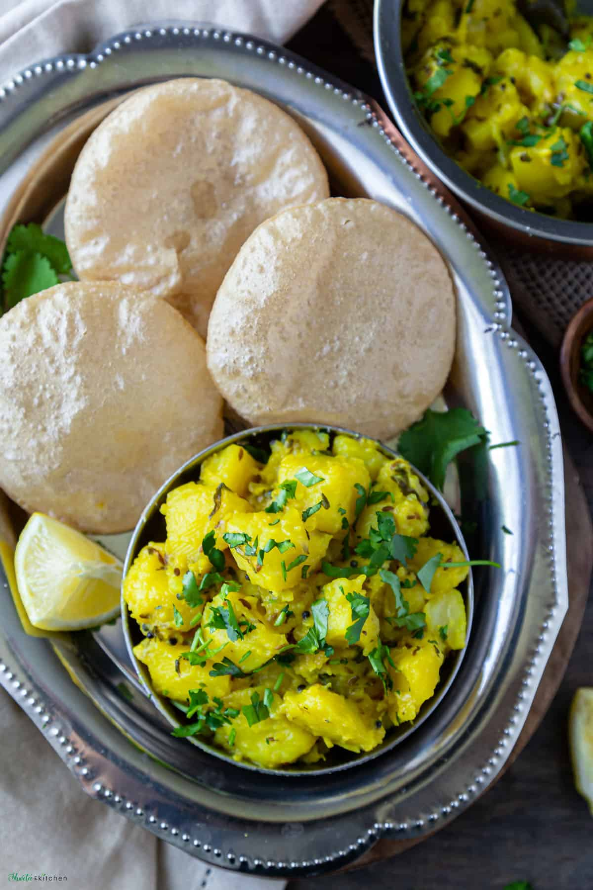 Oval Silver plate with bowl of batata bhaji and 3 pooris