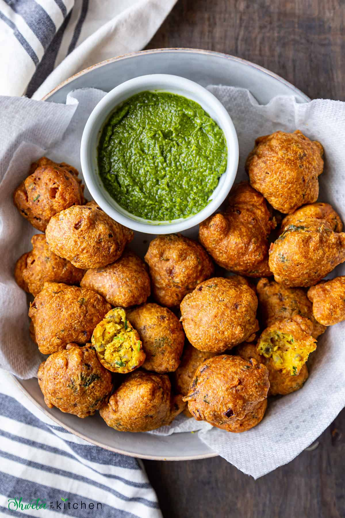plate full of pakora and green chutney in a bowl