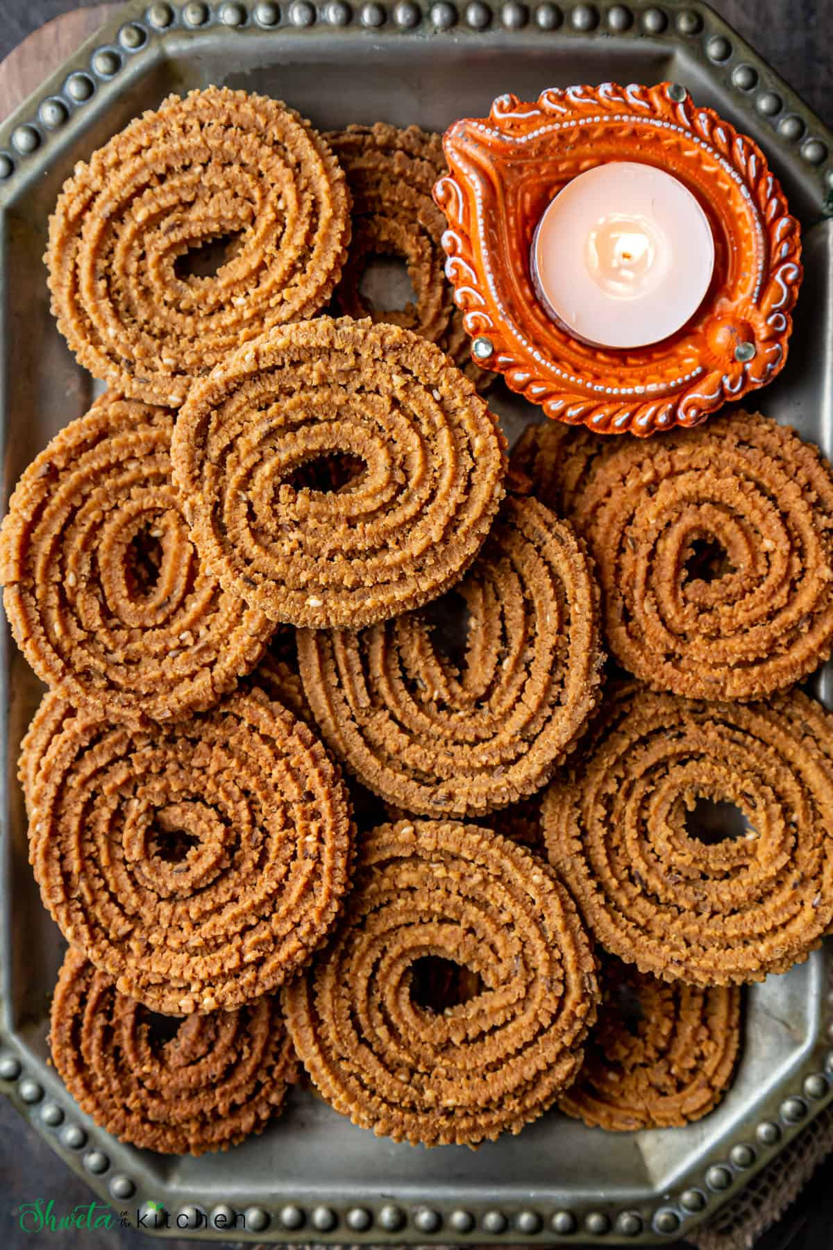 Chakalis on plate with Diwali lamp in one corner.