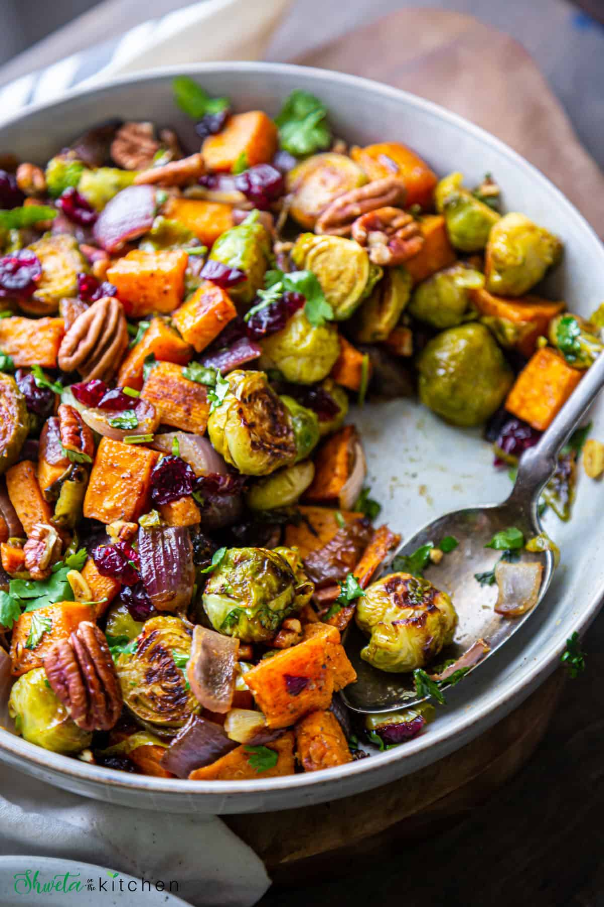Bowl of roasted sweet potatoes and brussels sprouts with a spoon