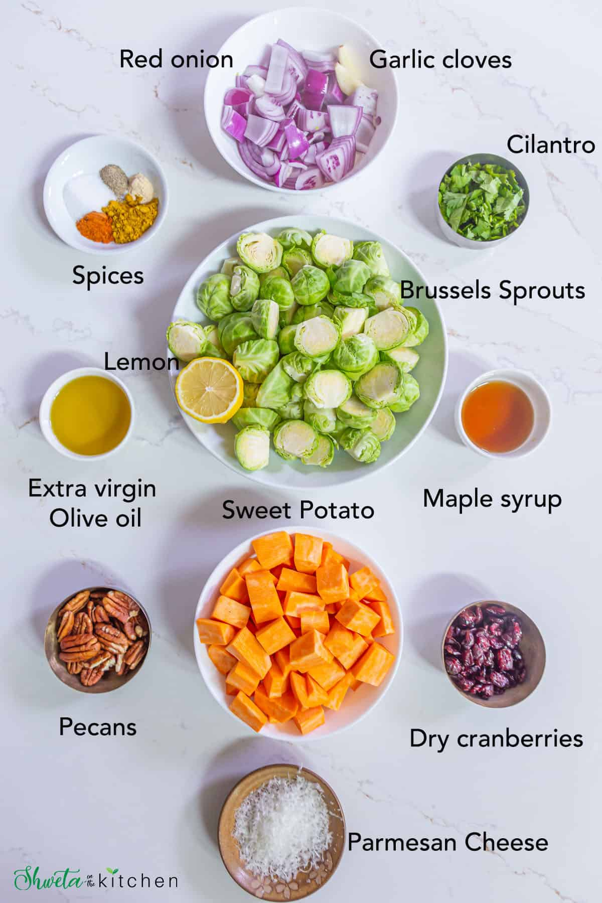 Ingredients for roasted brussels sprouts and sweet potatoes laid out in bowls on white surface