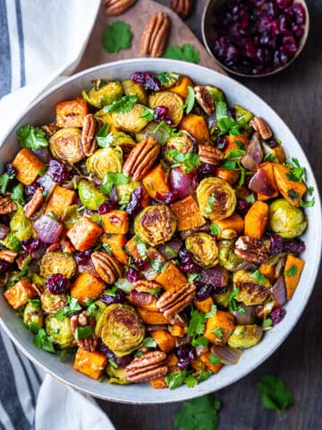 Bowl of roasted brussels sprouts and sweet potatoes with bowl of dry cranberries at side