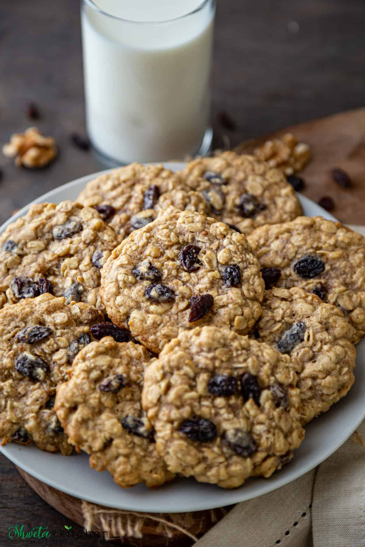heap of Oatmeal Raisin Cookies on a plate with glass of milk in background