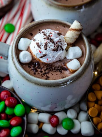 Hot chocolate in a mug topped with cream, marshmallows and rolled wafer