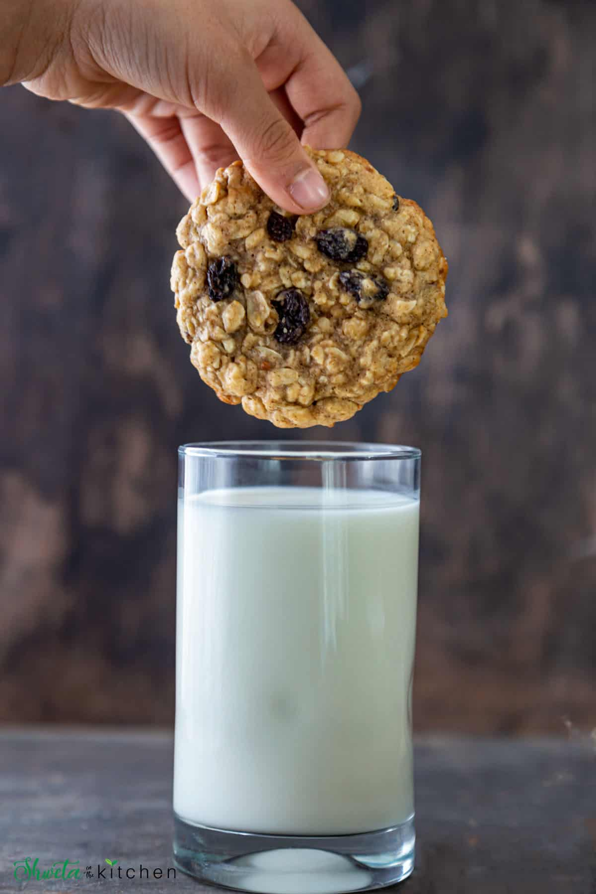 Oatmeal raisin cookie about to be dipped in glass of milk