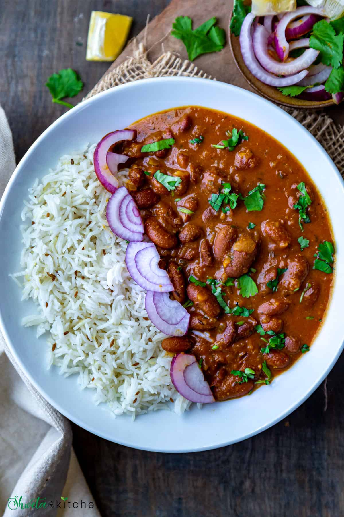 White bowl of rajma chawal (red kidney beans curry with rice) with onions in middle