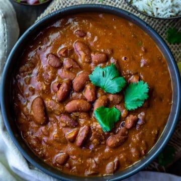 bowl of rajma masala with rice and salad on side