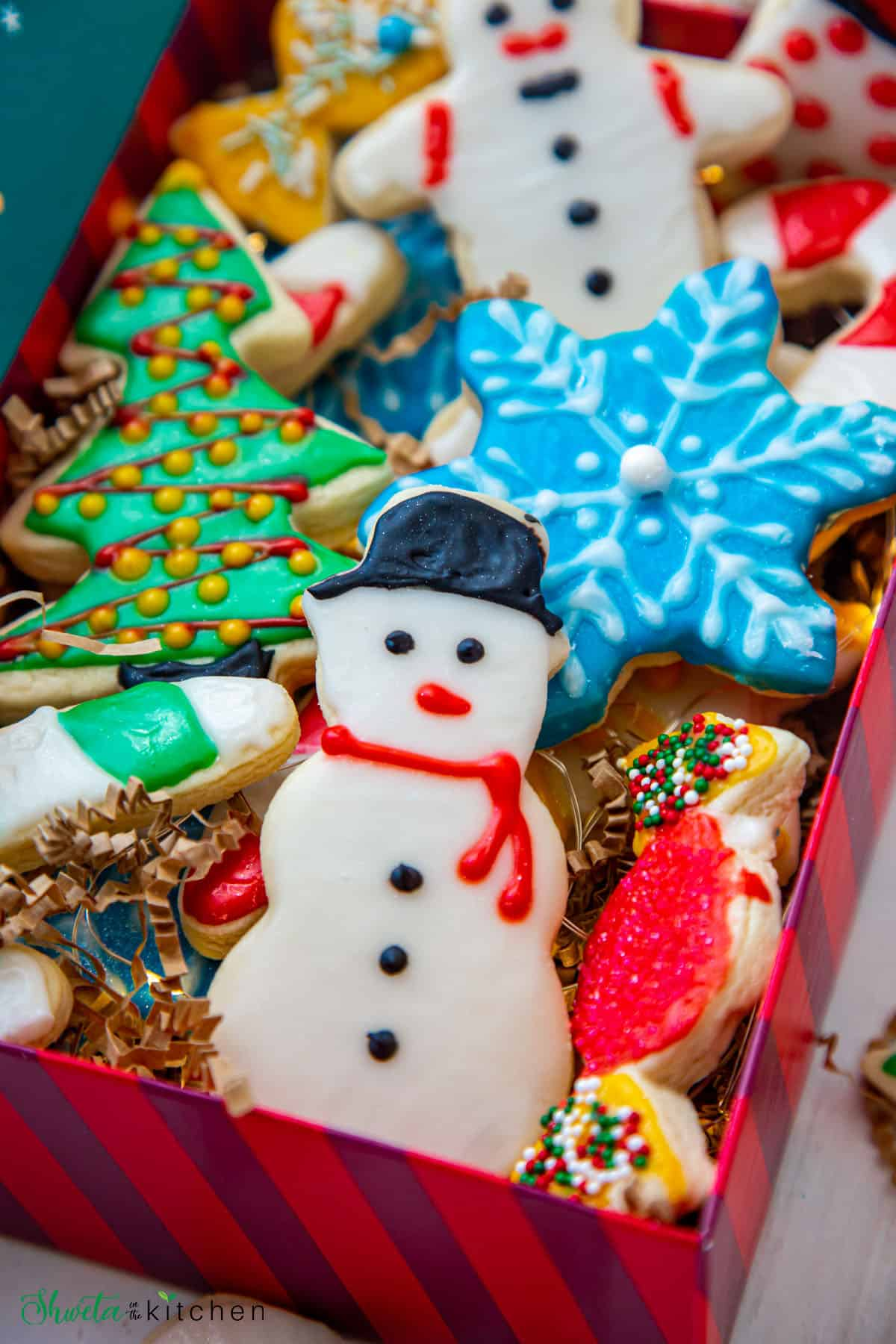Close up of snowman sugar cookie with other cookies in background
