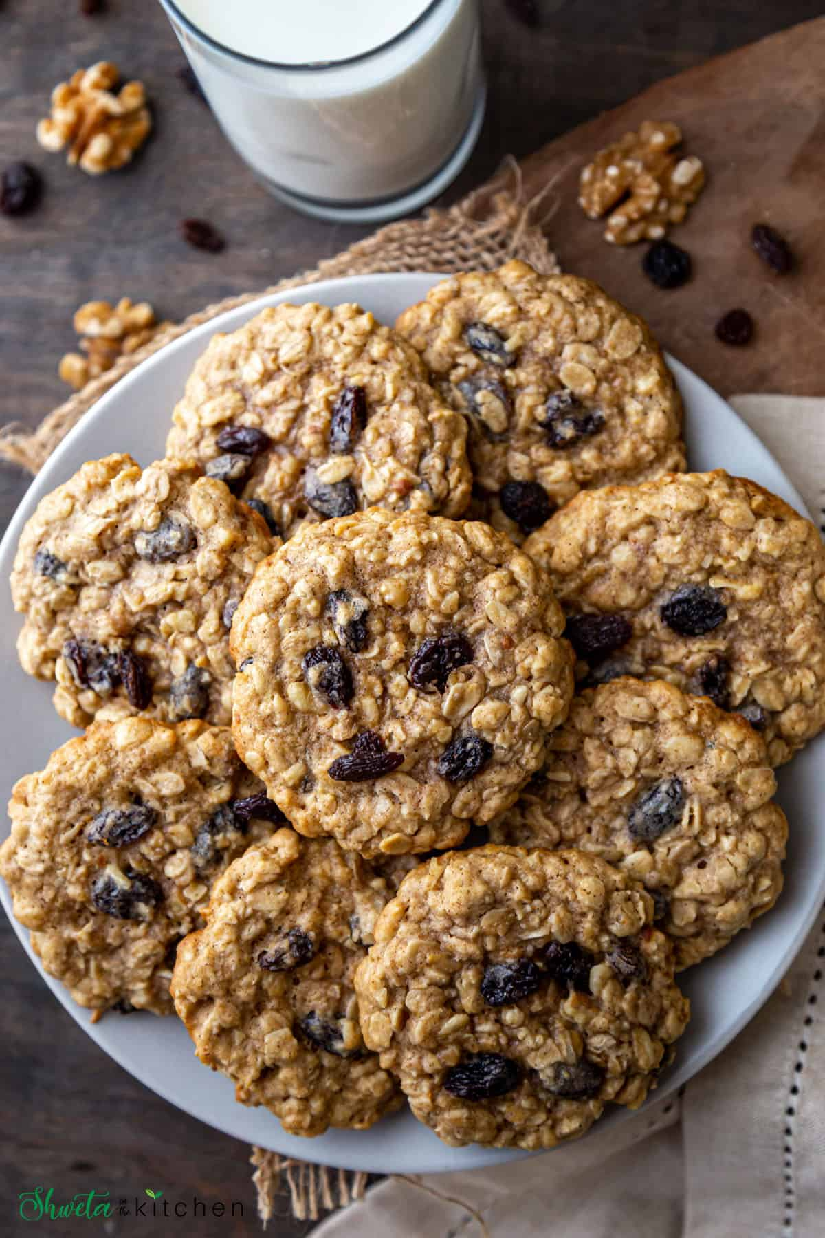 Heap of Oatmeal Raisin Walnut cookies on plate with glass of milk on the side