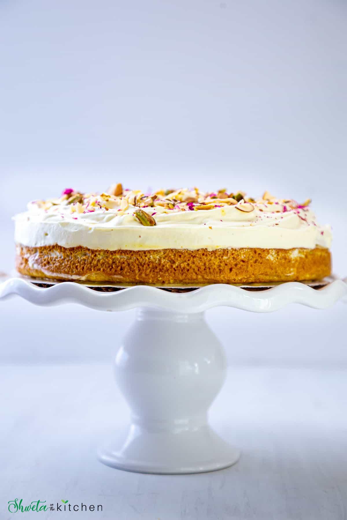 Side view of rasmalai cake on white cake stand