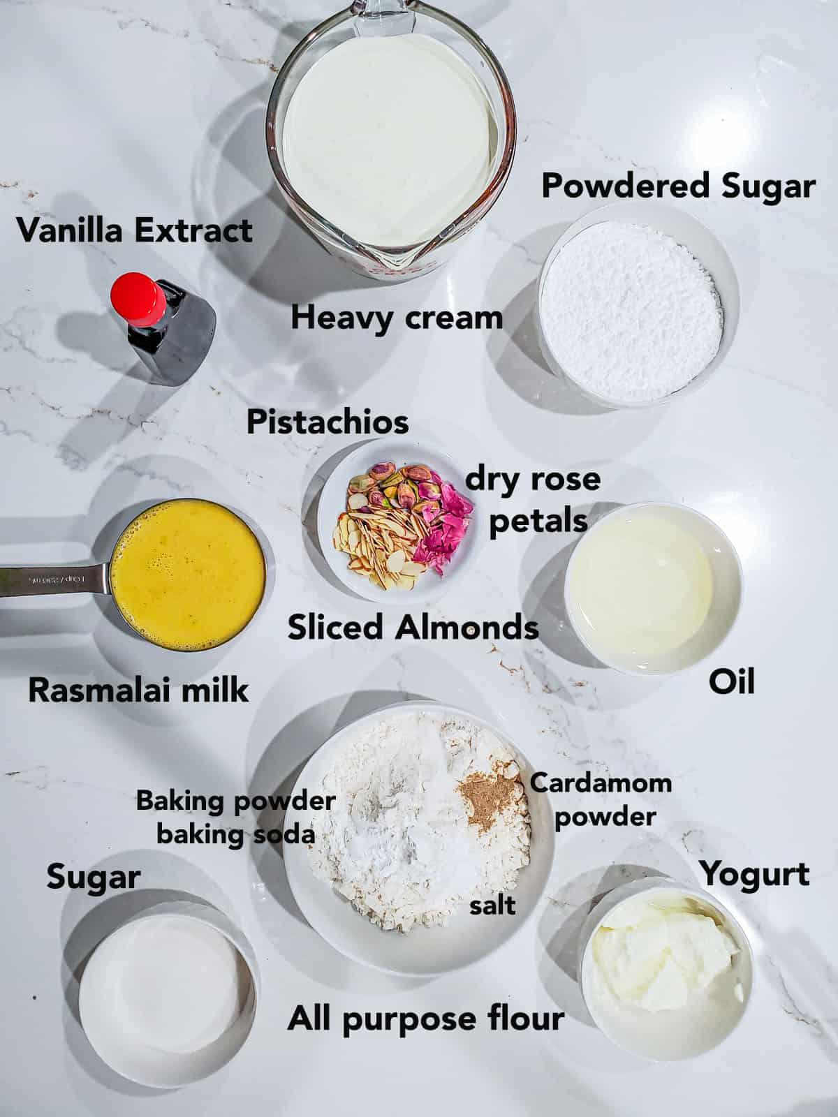 eggless rasmalai cake ingredients in bowls on white surface