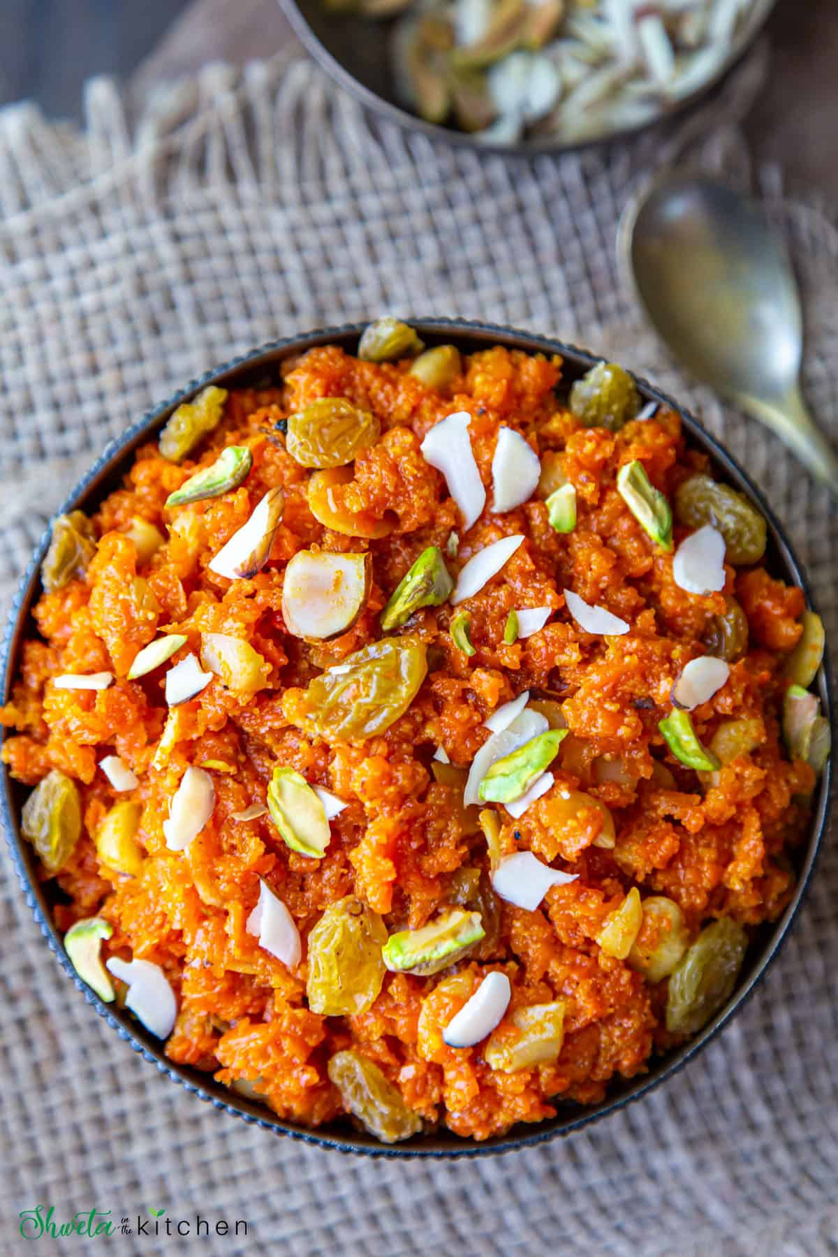 Carrot Halwa with Icecream in a bowl with spoon on side and bowl of nuts