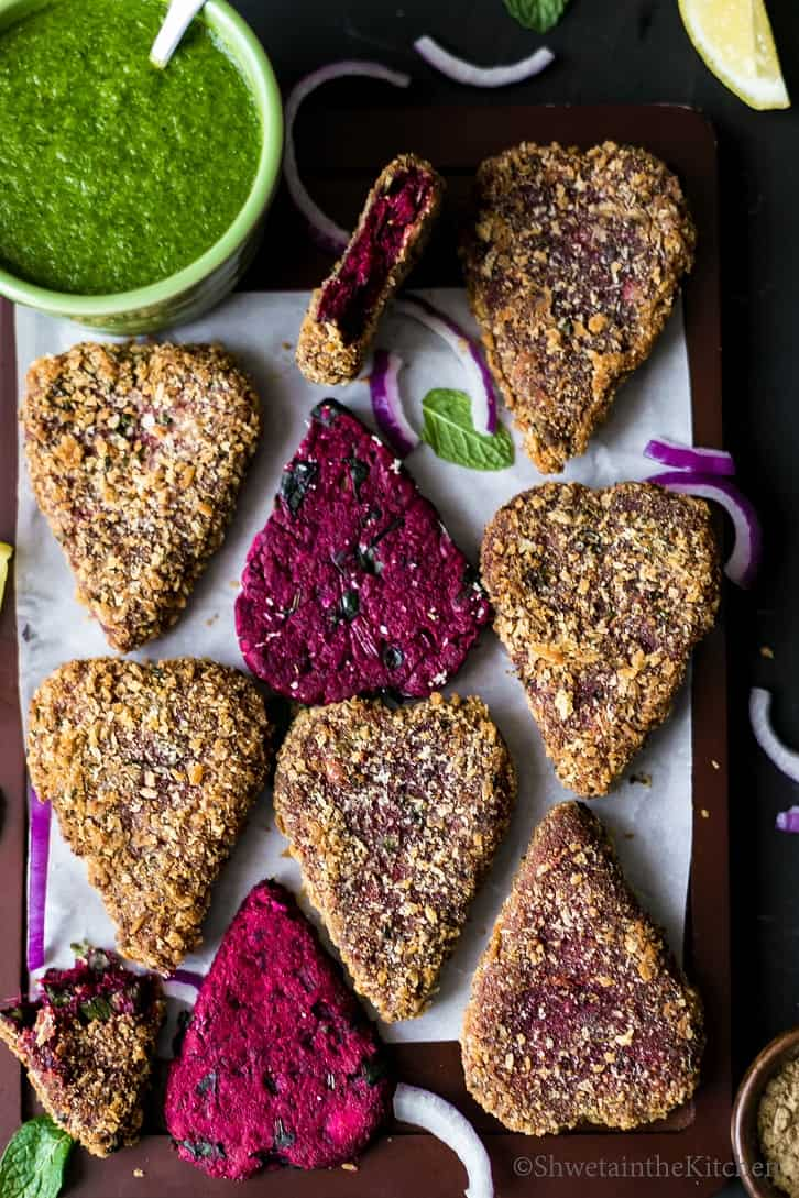 Beetroot cutlets with and without breading on a rectangular board.
