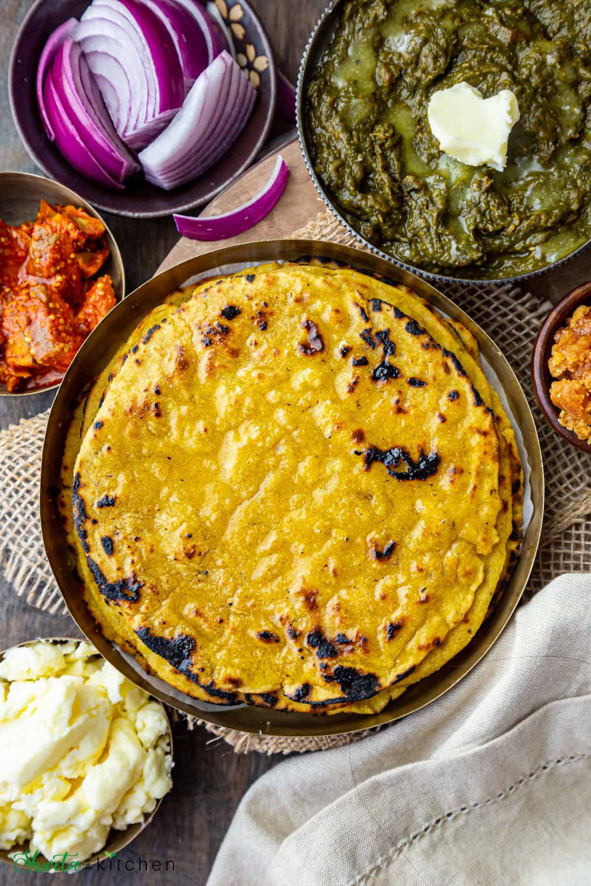 Makki ki roti on a plate with saag, jaggery, pickle, butter and onions on the side
