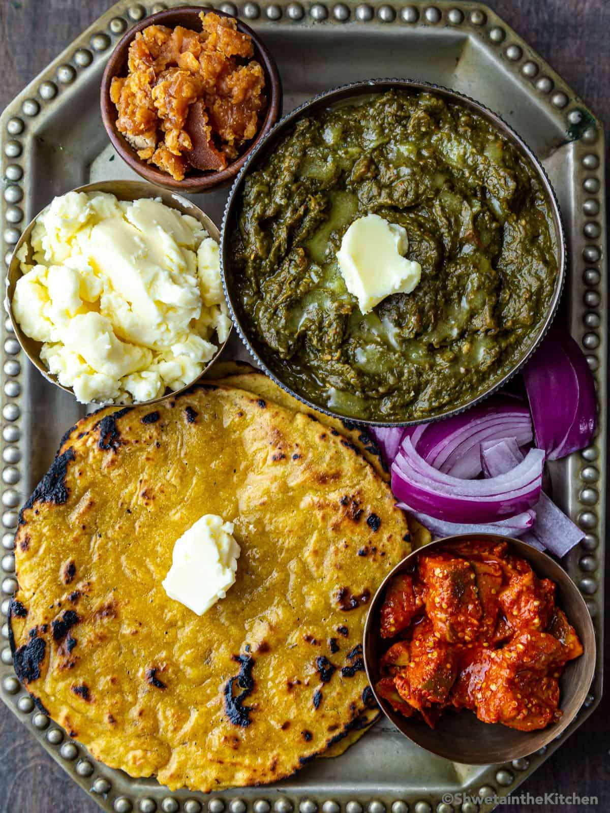 Makki ki roti Sarson ka saag along with white butter, jaggery, pickles and onions