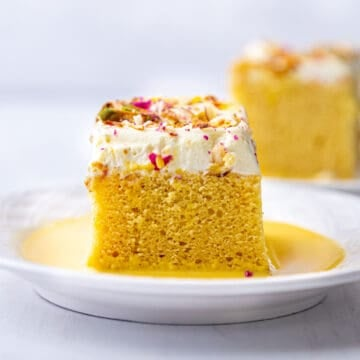 front view of rasmalai cake slice on a white plate