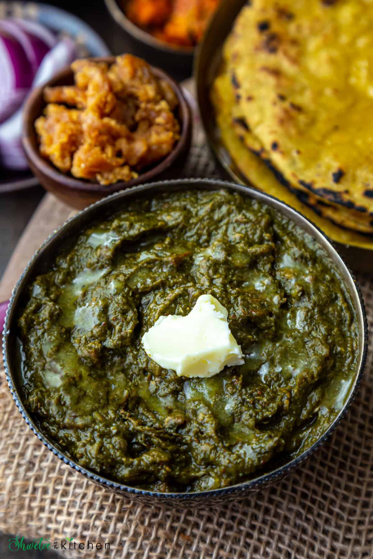 Side view of Sarson ka Saag in a bowl topped with white butter and makki ki roti and gud (jaggery) on the side