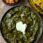 Sarson ka Saag in a bowl topped with white butter and makki ki roti and gud (jaggery) on the side