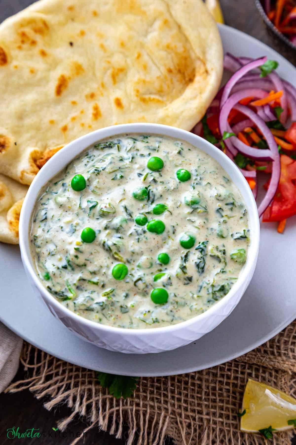 Bowl of Methi Matar Malai with naan and mix veg salad on a plate