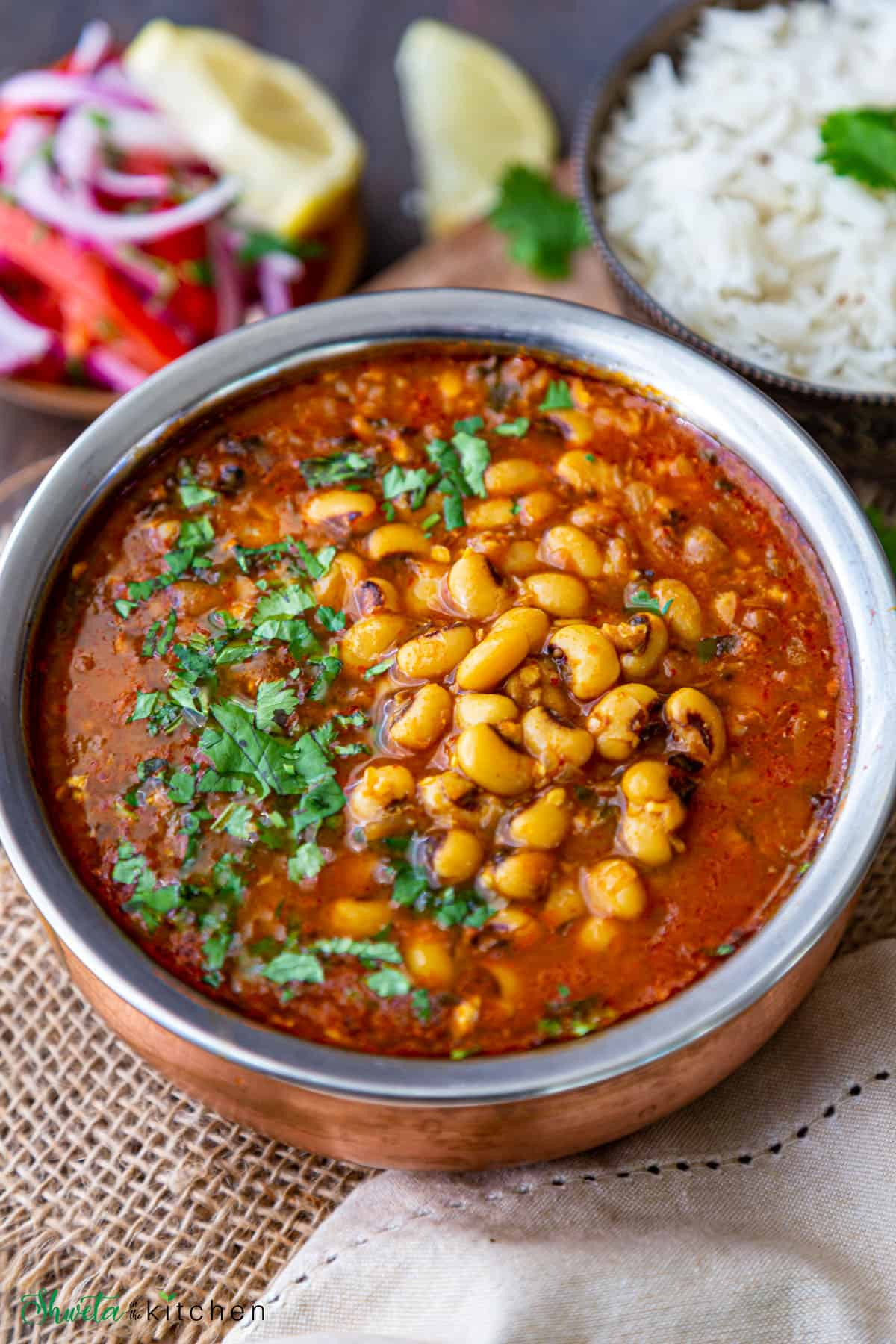 Side view of Lobia (black eyed peas) curry in a bowl on a wooden surface with rice and salad on the side