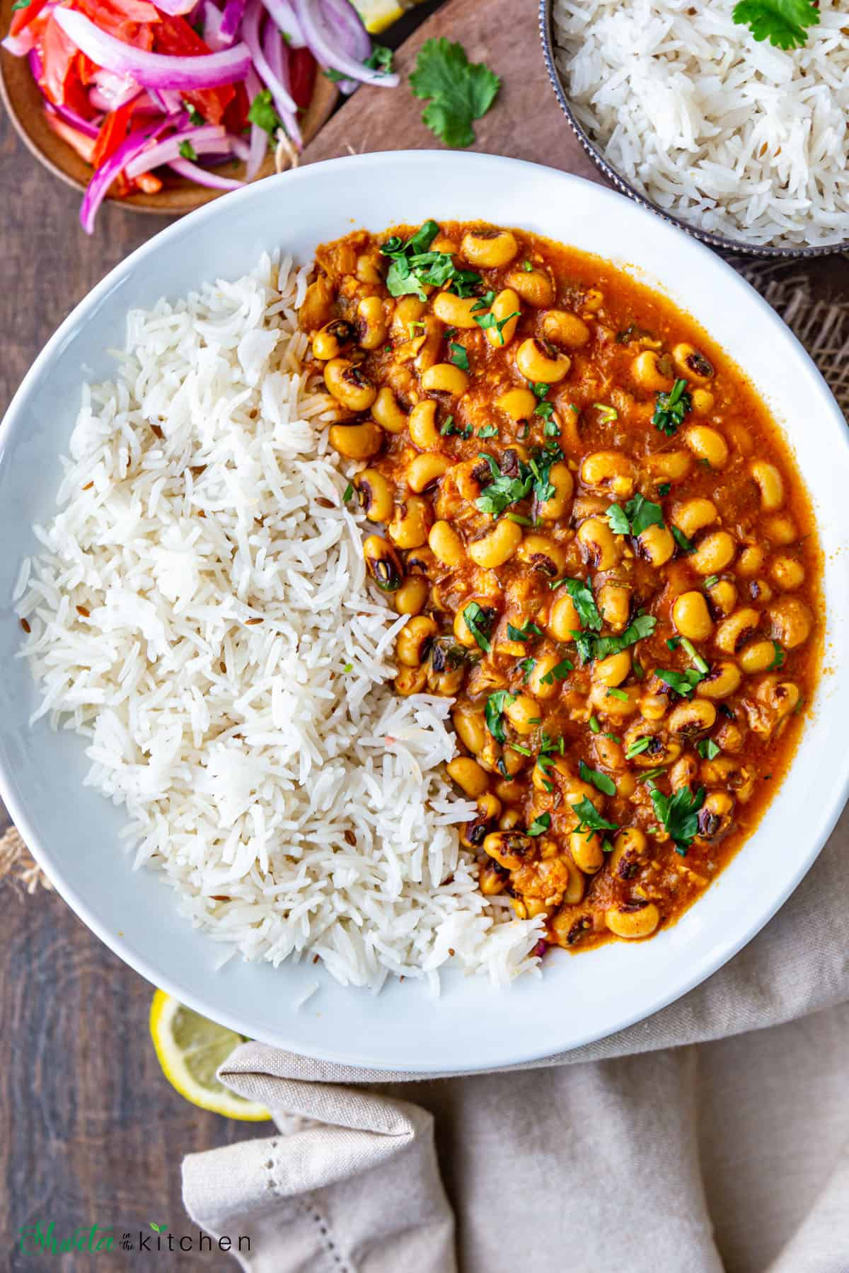 White bowl filled with rice and lobia (black eyed peas) Curry