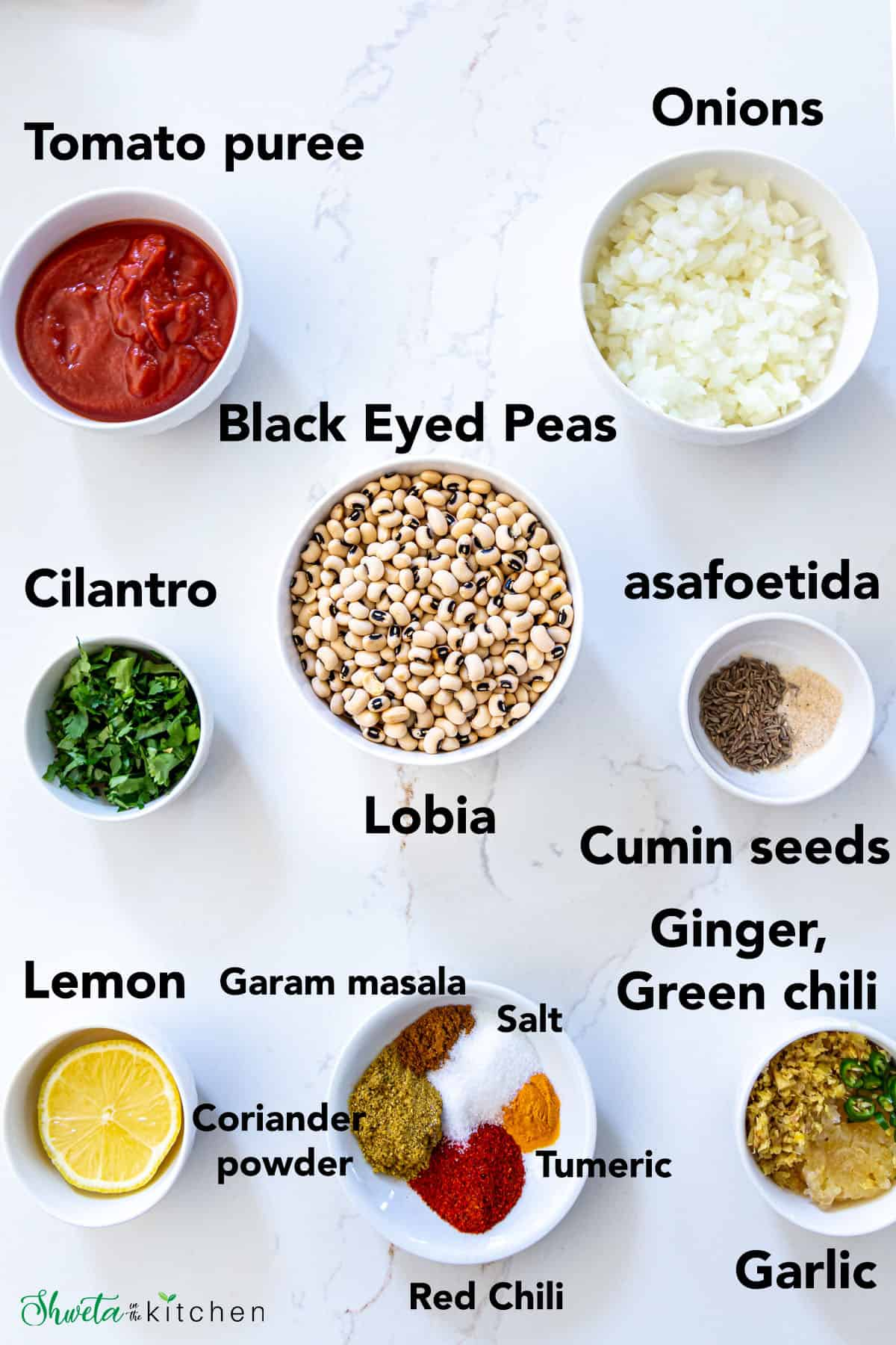 Ingredients for Lobia (black eyed peas curry) in bowls on white surface
