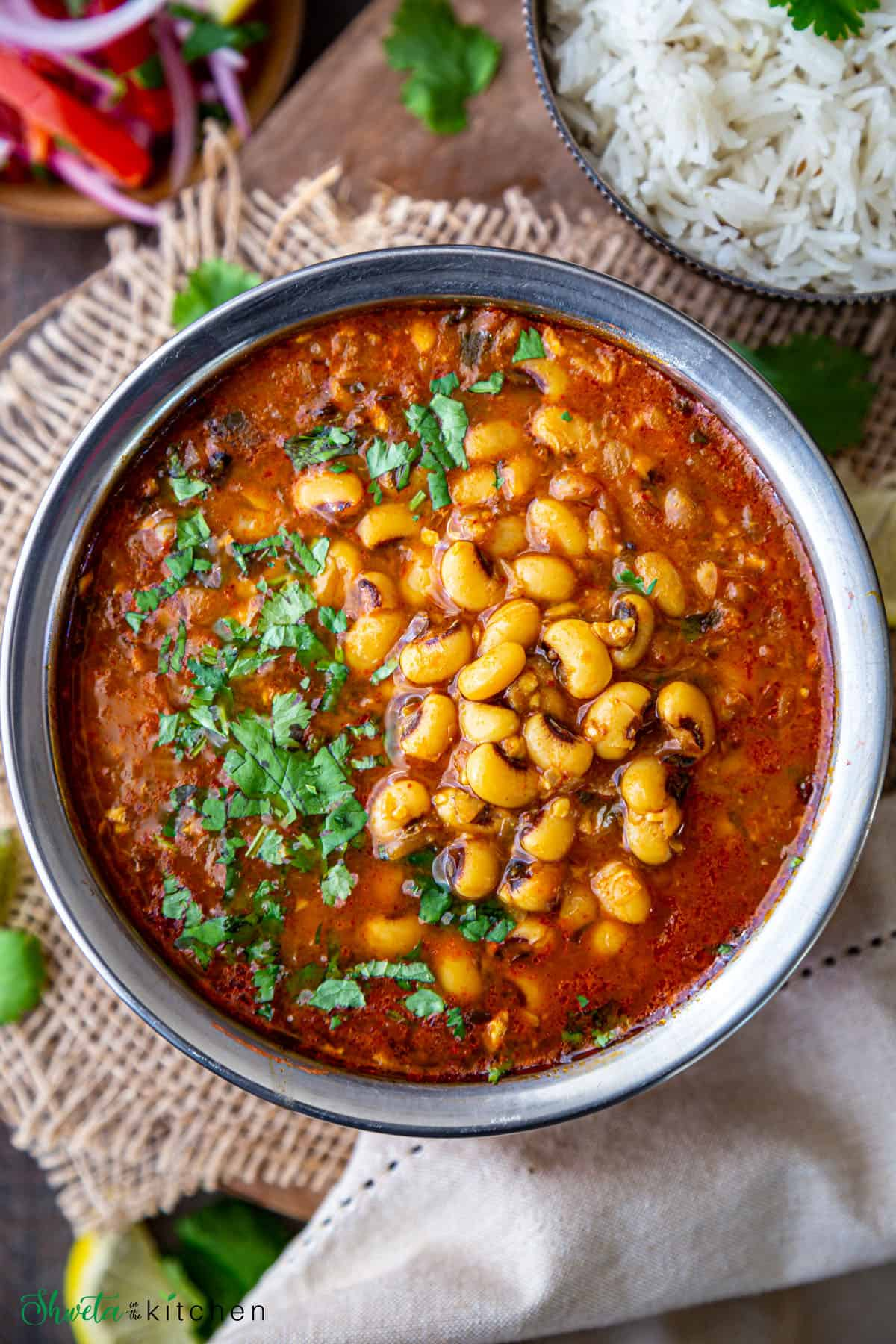 Lobia (black eyed peas) curry in a bowl on a wooden surface with rice and salad on the side