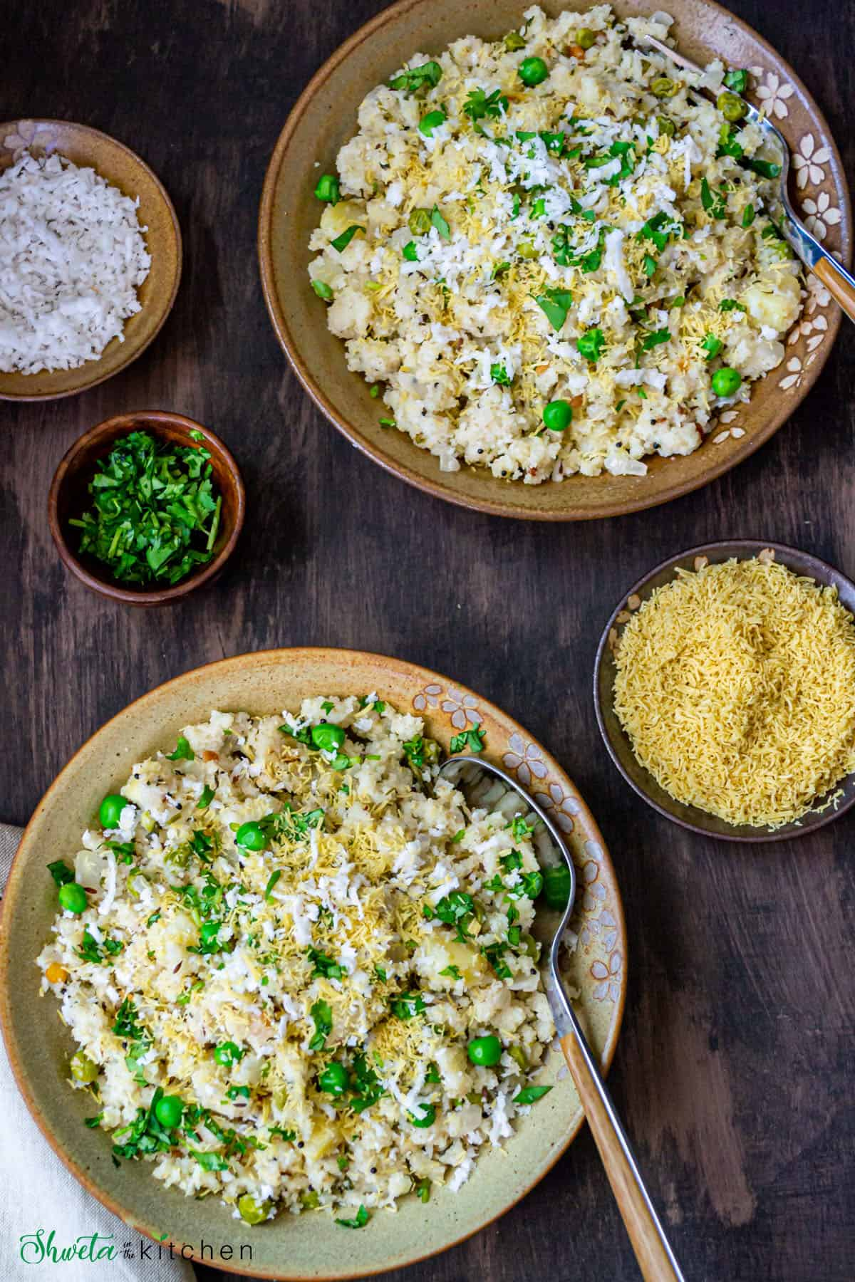Two bowls of rava upma with spoons along with bowls on sev, cilantro and coconut