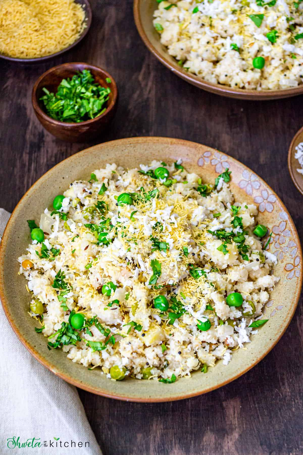Rava upma served in a large bowl next to a small bowl of fresh cilantro.