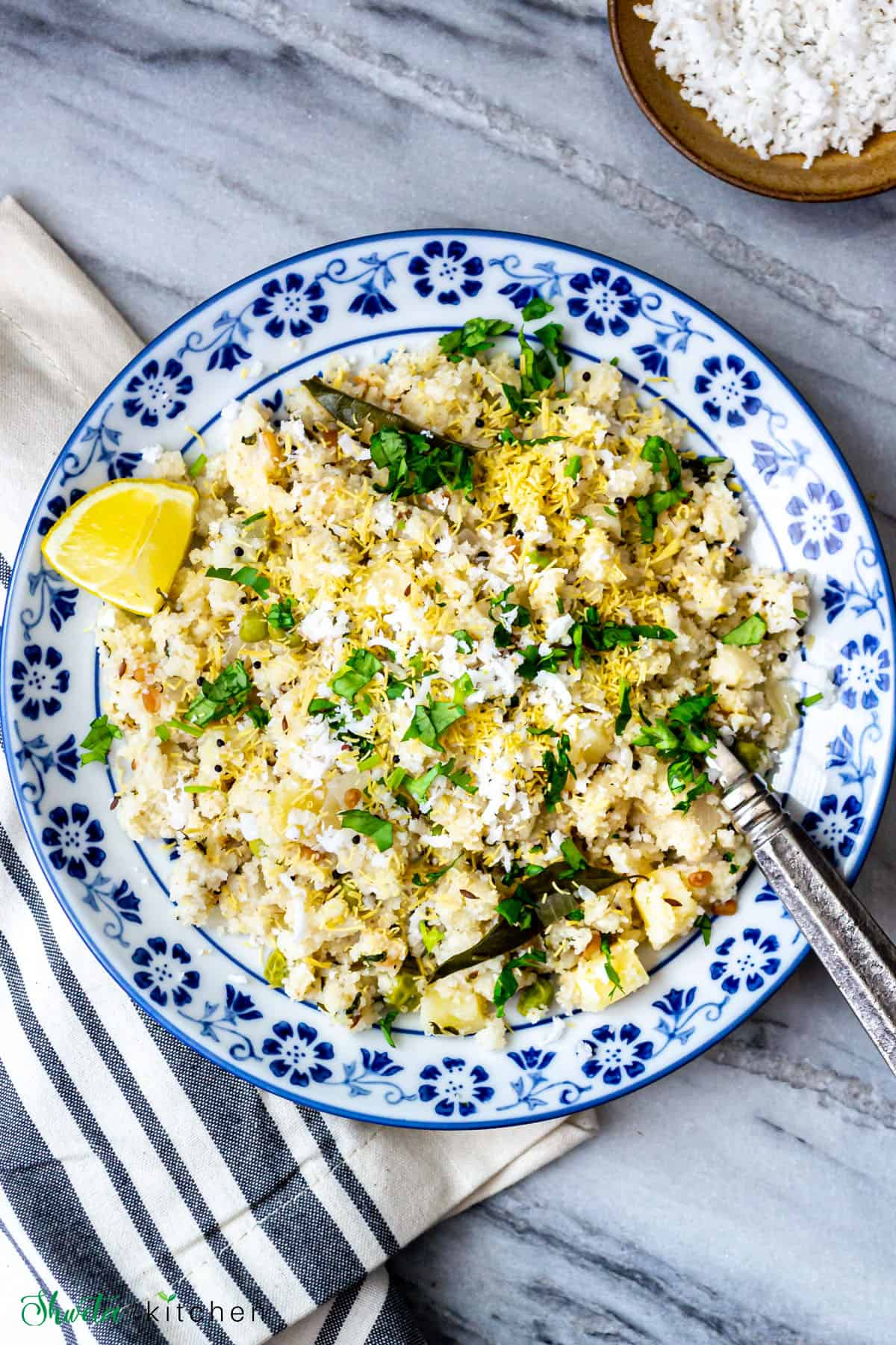Upma served in a white an blue patterned bowl with a wedge of lemon and fresh herbs