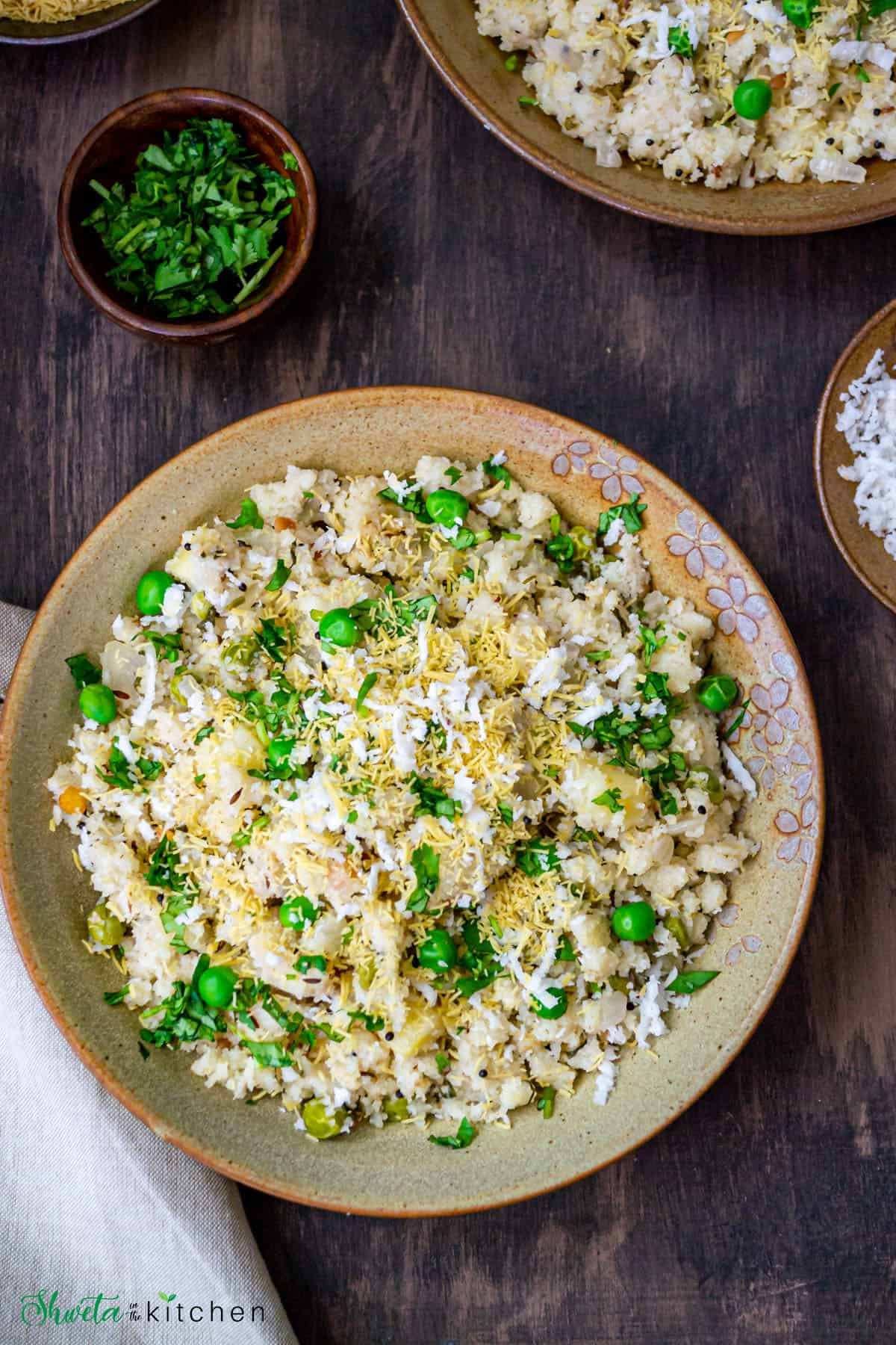 Top view of bowl of rava upma garnished with green peas and sev, and coconut.