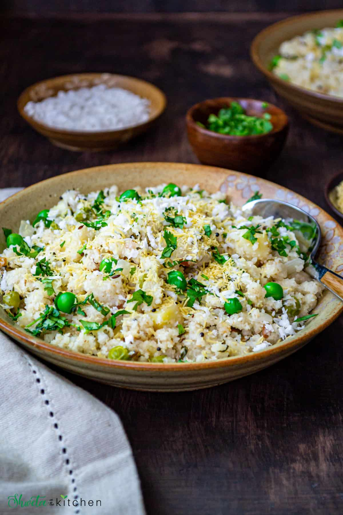 Rava upma served in a bowl with a spoon and garnished with fresh cilantro