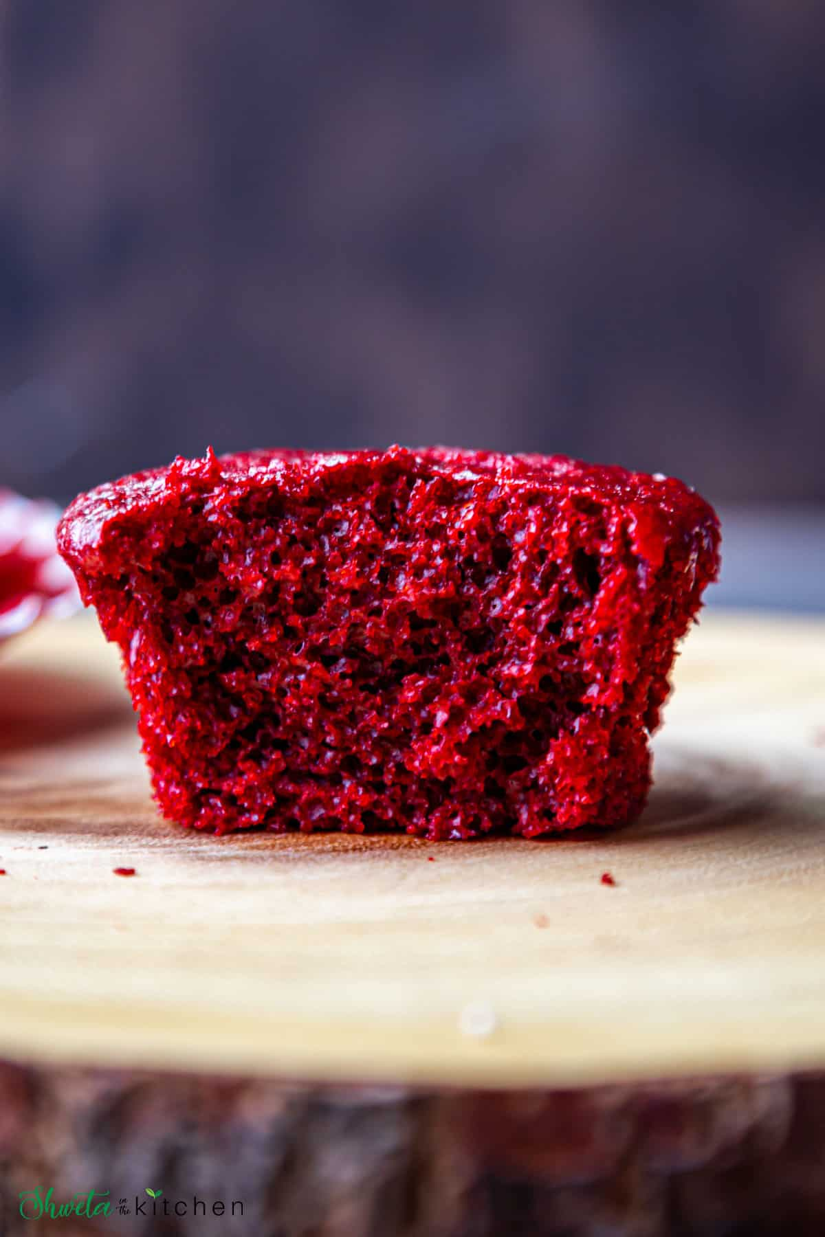 eggless Red velvet cupcake cut in half showing the crumb texture