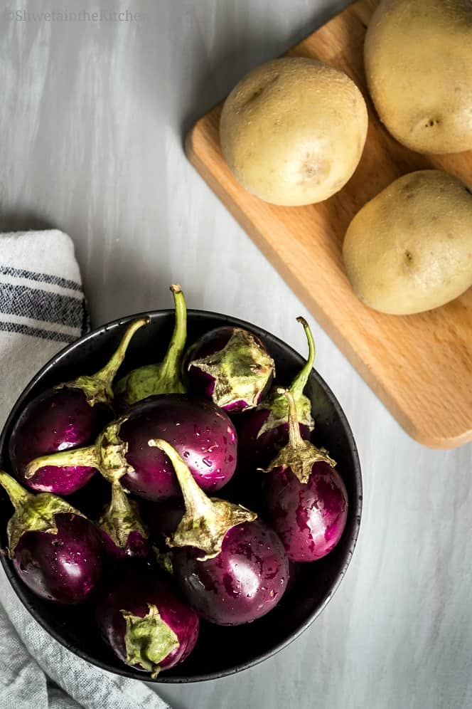 Potatoes on cutting board and and eggplants in bowl.