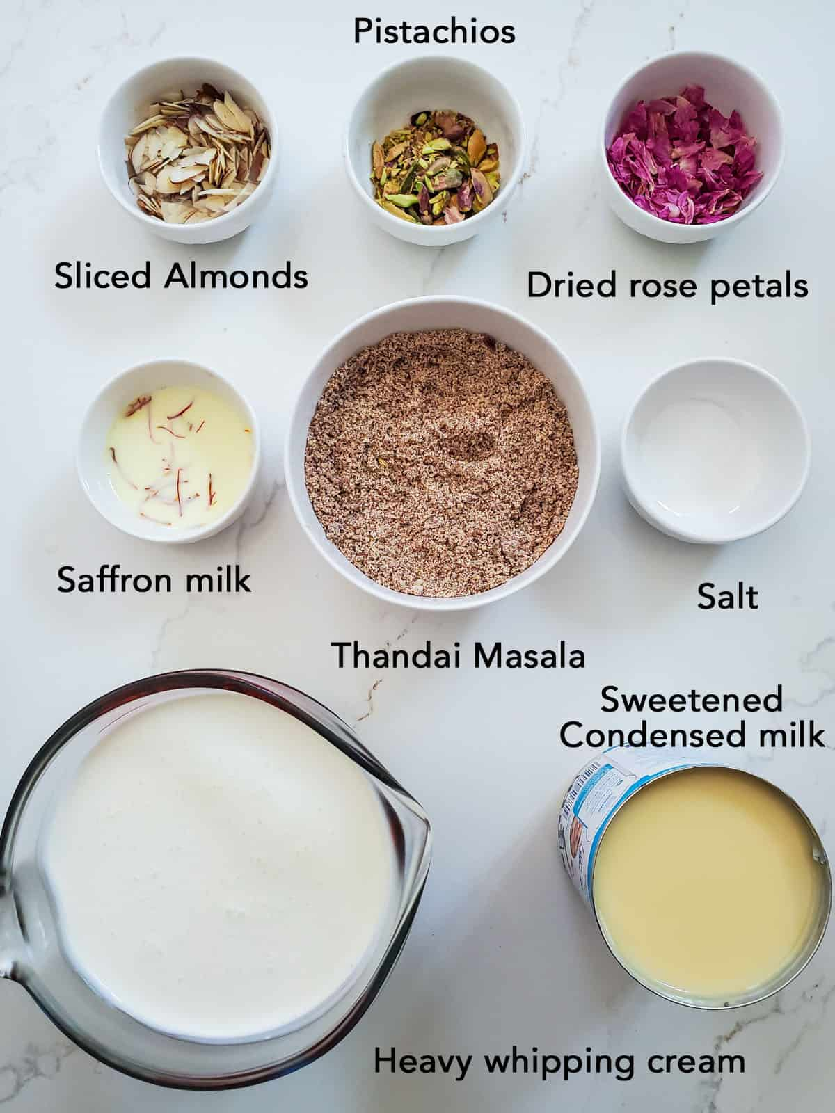 Thandai icecream ingredients in bowls on white surface