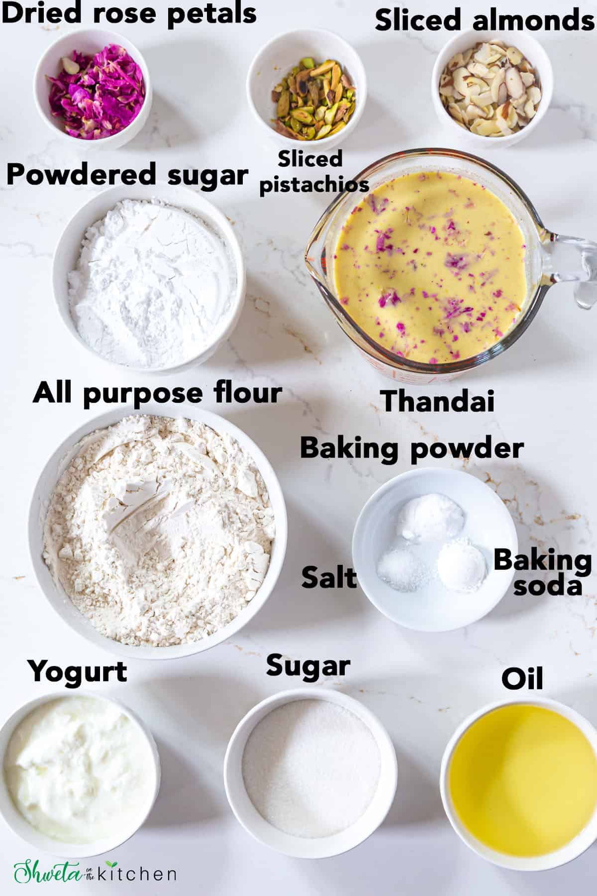 Thandai cake ingredients laid out in bowls on white surface