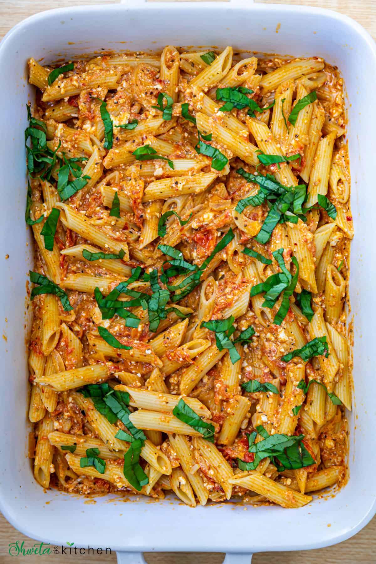 Baking dish full of baked feta pasta garnished with shredded basil