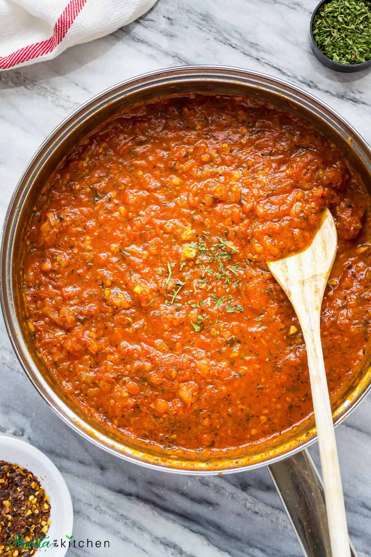 Arrabbiata sauce in a silver pot with a wooden spoon in it