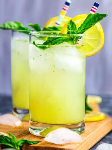 Front view of two glasses of basil ginger lemonade garnished with lemon and basil leaves