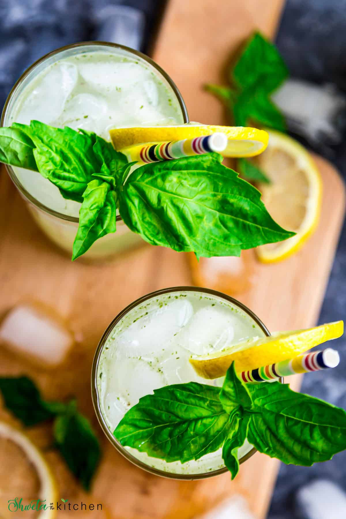 Top view of Two glasses of basil ginger lemonade garnished with lemon and basil leaves