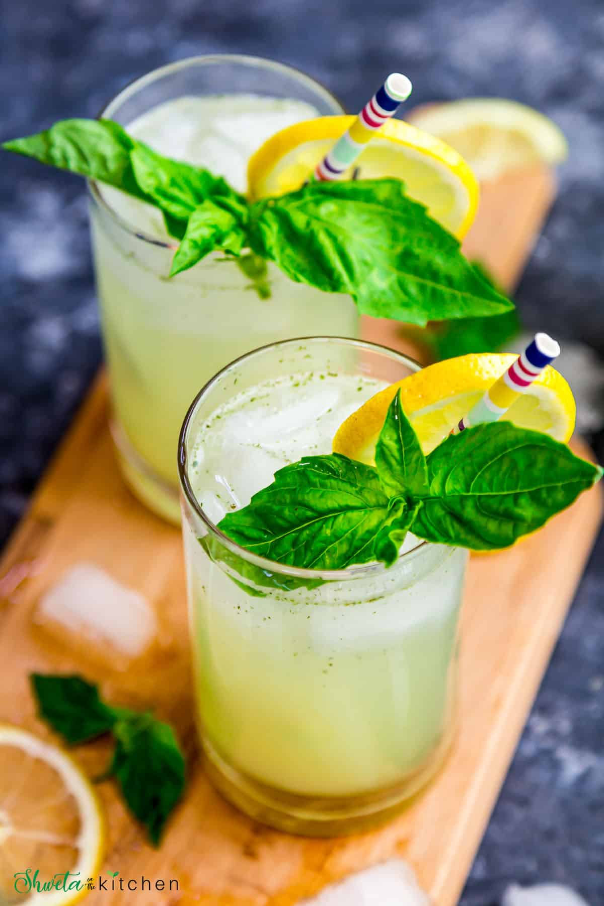 Side top view of Two glasses of basil ginger lemonade garnished with lemon and basil leaves
