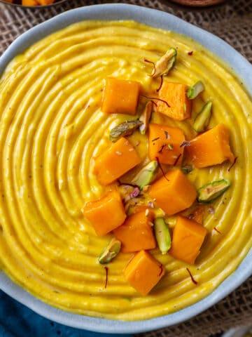 Blue bowl full of Mnag shrikhand garnished witth cut mangoes and pistachios