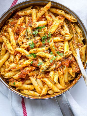 Arrabiatta sauce stired into pasta in a pot and garnished with fresh parsley