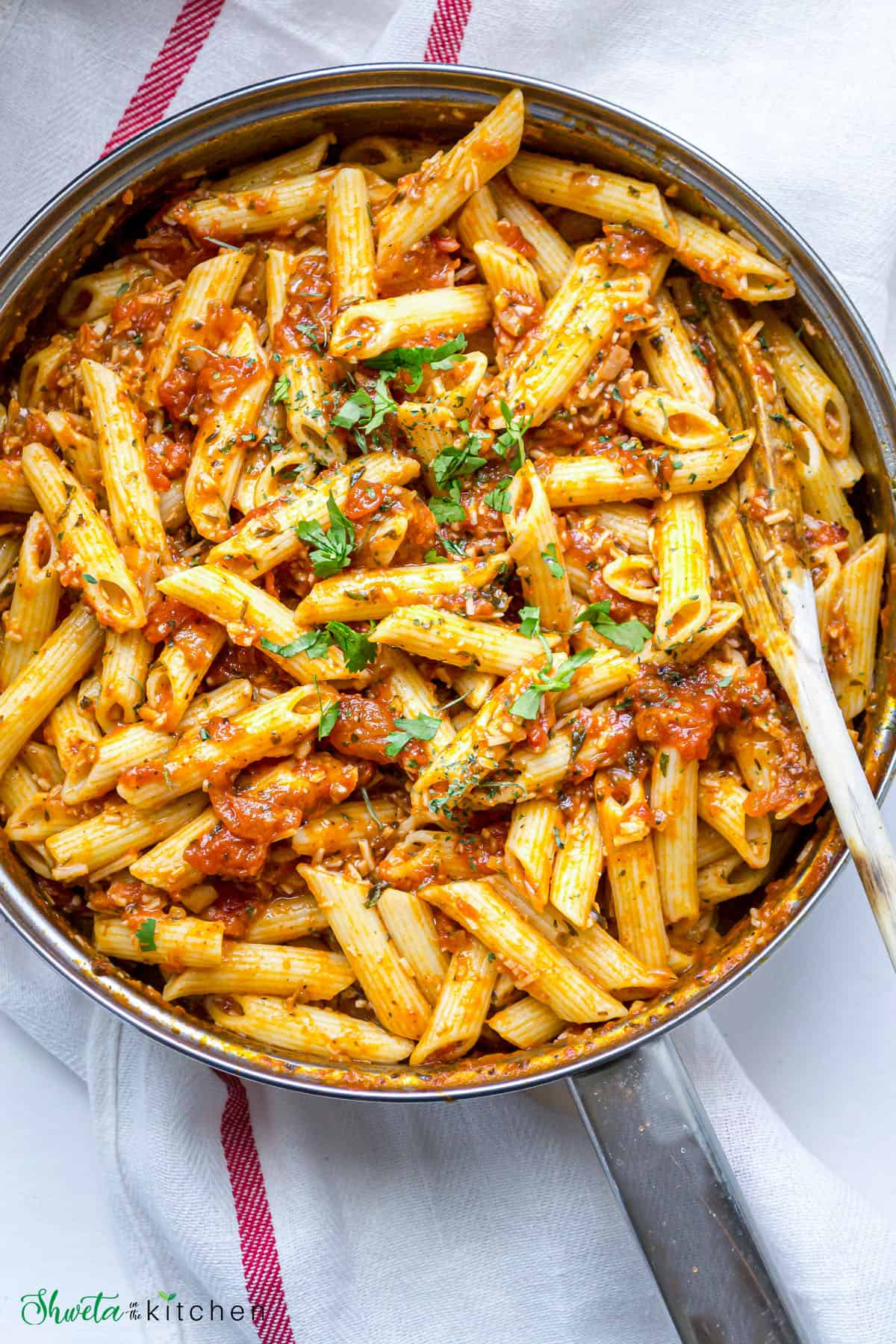 Arrabiata sauce stirred into pasta in a pot and garnished with fresh parsley