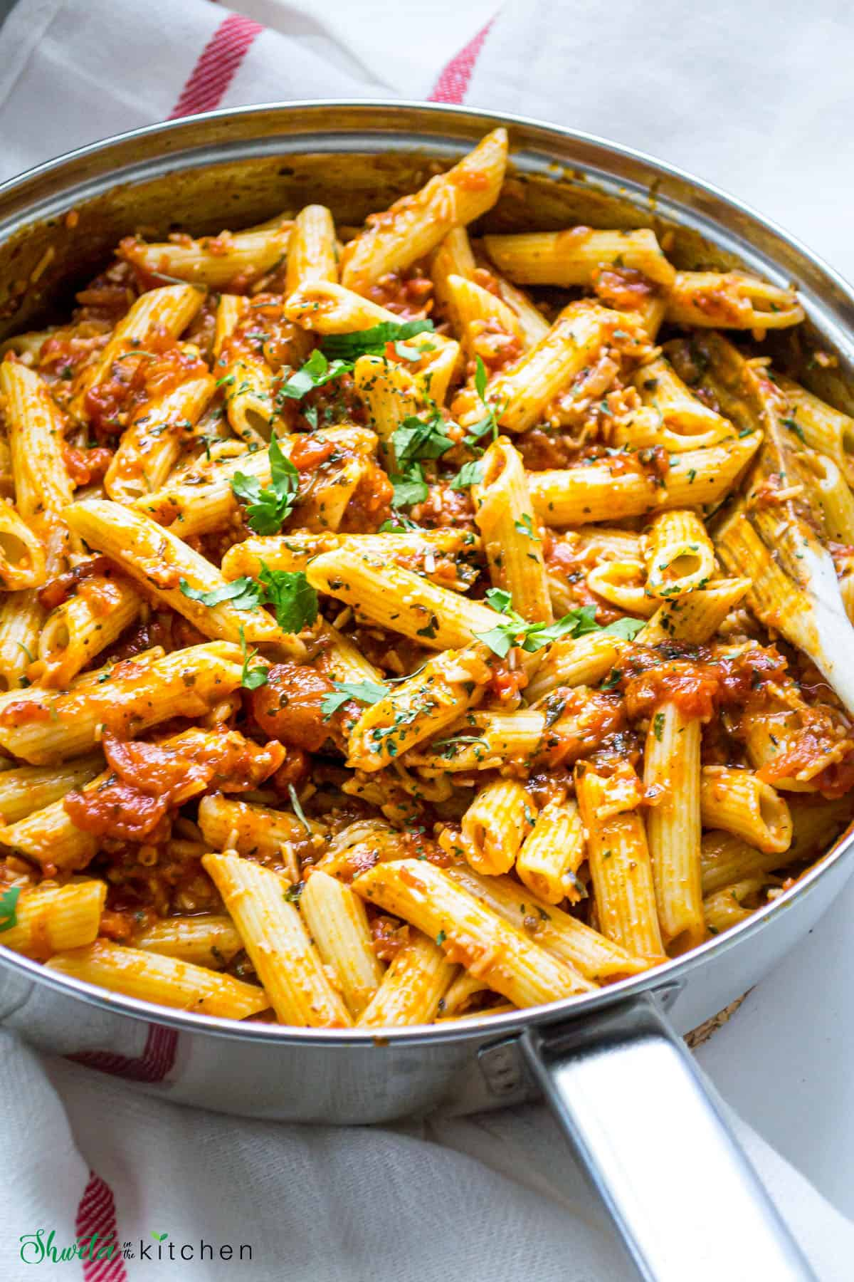 A wooden spoon in a pan of penne pasta with arrabbiata sauce