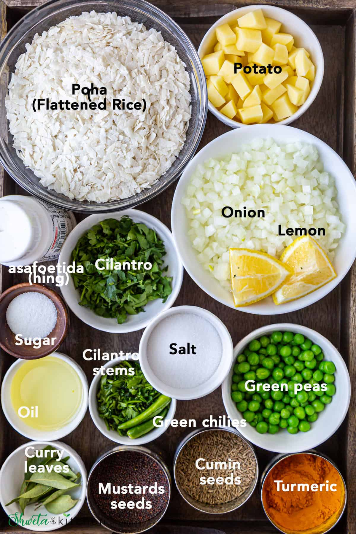 Ingredients for poha in bowls on wooden tray